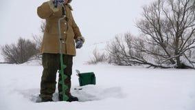 Pescador, agujero agujereado en el lago nevado en busca de un buen lugar pesquero metrajes