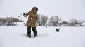 Pescador, agujero agujereado en el lago nevado en busca de un buen lugar pesquero almacen de video