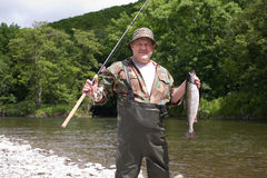 Pescador alegre que sostiene salmones rosados. Imagenes de archivo