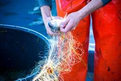 pescador ao limpar a rede de pesca dos peixes Fotos de Stock