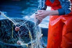 pescador ao limpar a rede de pesca dos peixes Fotografia de Stock