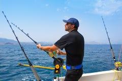 Pescador azul del mar en barco de pesca con cebo de cuchara con cebo de cuchara con el downrigger Imagen de archivo
