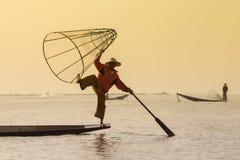 Pescador birmano en pescados de cogida del barco de bambú de la manera tradicional con la red hecha a mano Lago Inle, Myanmar, Bi Fotos de archivo libres de regalías