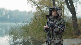 Pescador bonito da mulher na camuflagem e nas luvas de couro que guardam uma vara de pesca e para seduzir para peixes video estoque