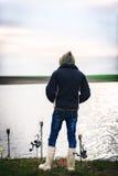 Pescador cerca de sus cañas de pescar en la puesta del sol que espera un pescado Foto de archivo libre de regalías
