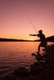 Pescador Checking Lure no por do sol imagens de stock