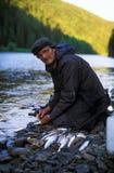 Pescador Cleans um peixe no banco de rio Fotos de Stock Royalty Free