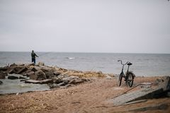 Pescador com a bicicleta na costa do Golfo da Finl?ndia no tempo nebuloso fotos de stock