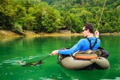 Pescador com a captura da truta arco-íris, Eslovênia imagem de stock