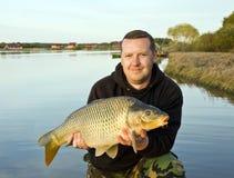 Pescador com a carpa no céu crepuscular Fotografia de Stock Royalty Free