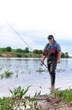Pescador com giro no banco do rio. Fotos de Stock