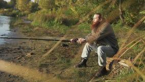 Pescador com pesca longa da barba no banco de rio Homem que espera emocionalmente os peixes Pesca do rio video estoque