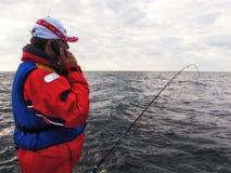 Pescador com telefone móvel imagens de stock
