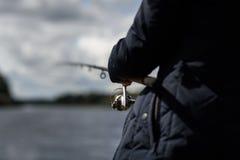 pescador com um alimentador na frente do rio foto de stock