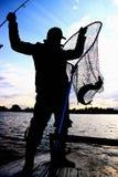 Pescador com um peixe de travamento no rio Fotografia de Stock
