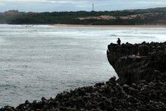 Pescador con el giro en la playa en rocas de la playa en Bali Imagen de archivo
