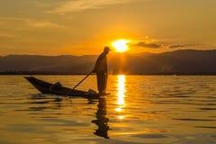 Pescador con el rowing de la pierna durante puesta del sol, lago del inle en Myanmar ( imágenes de archivo libres de regalías