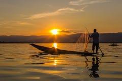 Pescador con el rowing de la pierna durante puesta del sol, lago del inle en Myanmar ( foto de archivo