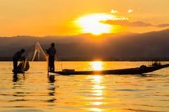 Pescador con el rowing de la pierna durante puesta del sol, lago del inle en Myanmar ( Imagen de archivo libre de regalías