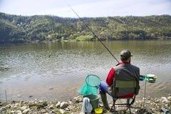 Pescador con el suyo detrás hacia la cámara que se sienta en la costa del río que disfruta de pescar con caña y de la naturaleza  fotos de archivo libres de regalías