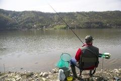 Pescador con el suyo detrás hacia la cámara que se sienta en la costa del río que disfruta de pescar con caña y de la naturaleza  foto de archivo