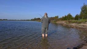 Pescador con la caña de pescar en agua metrajes