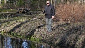 Pescador con la caña de pescar en el banco de río metrajes