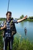Pescador con la perca en el río Chagan Foto de archivo libre de regalías