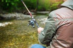 Pescador con la pesca con mosca en el río de la montaña Imagen de archivo libre de regalías