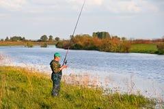 Pescador con la pesca de giro en pescados depredadores Fotos de archivo