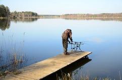 Pescador con la vaina de la barra, alimentadores, alarmas electrónicas de la mordedura en el embarcadero Imagen de archivo libre de regalías