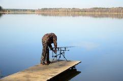 Pescador con la vaina de la barra, alimentadores, alarmas electrónicas de la mordedura en el embarcadero Fotos de archivo