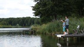 Pescador con los pescados de cogida de la barra de giro en el lago almacen de video