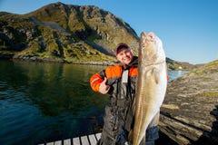 Pescador con los pescados enormes que muestran el pulgar Imágenes de archivo libres de regalías