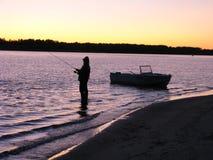 Pescador con un barco en el río Fotos de archivo