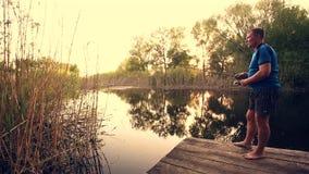Pescador con un pescado de cogida de la barra de giro en un río almacen de video