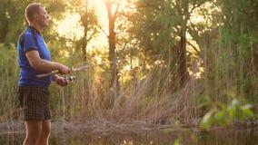 Pescador con un pescado de cogida de la barra de giro en un río metrajes