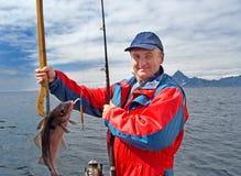 Pescador con un pescado en la isla de Lofoten Fotos de archivo libres de regalías