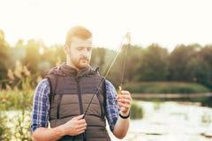 Pescador con una cogida de la barra y del cebo de giro (señuelo, wobbler) imágenes de archivo libres de regalías