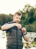 Pescador con una cogida de la barra y del cebo de giro (señuelo, wobbler) imagenes de archivo