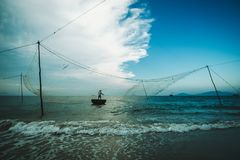 Pescador con una malla en un barco redondo de la costa de Vietnam Fotografía de archivo