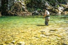Pescador da mosca que flyfishing no rio Fotografia de Stock
