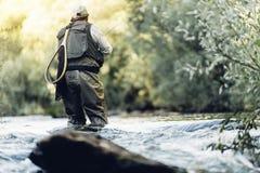 Pescador da mosca que usa a haste flyfishing Fotografia de Stock