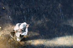 Pescador da mosca que usa a haste flyfishing Fotografia de Stock Royalty Free
