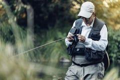 Pescador da mosca que usa a haste flyfishing Imagens de Stock