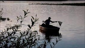 Pescador da silhueta no lago Lipno video estoque