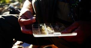 Pescador de la mosca que quita cebo de la caja de aparejos almacen de metraje de vídeo