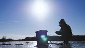 Pescador de la silueta en el hielo en el lago congelado en invierno Concepto de la afición de las vacaciones de invierno y de la  almacen de video