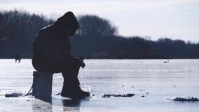 Pescador de la silueta en el hielo en el lago congelado en invierno Concepto de la afición de las vacaciones de invierno y de la  almacen de metraje de vídeo