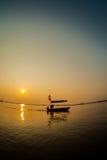 Pescador de la silueta en la puesta del sol. Imagenes de archivo